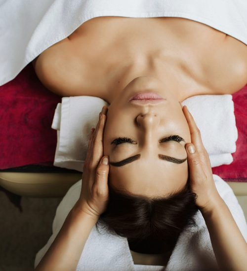 Attractive brunette woman getting massage spa treatment lying on a massage table, hands working on massaging woman's head. Relaxing facial massage at spa salon, top view.