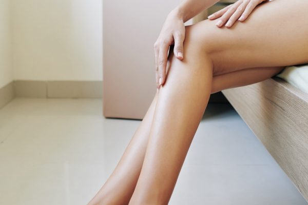 Woman applying body moisturizer
